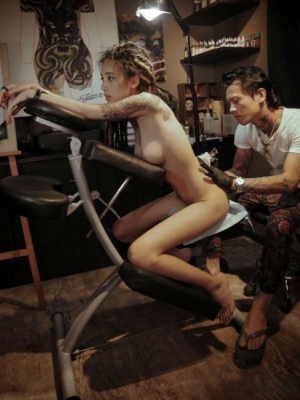 Nude girl getting inked